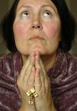 Older woman in prayer. Older woman with her hands up in prayer; focus is on the hands holding the cross Royalty Free Stock Images