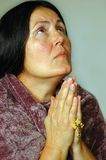 Older woman in prayer. Older attractive woman praying with a Christian cross Royalty Free Stock Image