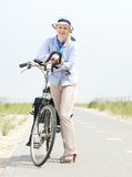 Older woman relaxing with bike on countryside path Stock Photo