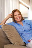 Older woman relaxing at home on sofa Royalty Free Stock Photos