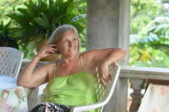 Older woman resting at tropical resort Royalty Free Stock Photography