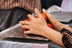 Older woman`s hands balancing tomatoes on a scale in farmers market with blurred background - selective focus stock images