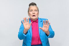 Older woman scared, have fear face. Aged woman scared, have fear face. Emotion and feelings Portrait expressive grandmother with light blue suit and pink shirt stock photos