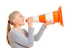 Older woman screams in pylon as a megaphone stock image