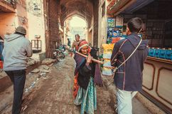 Older woman shopping and crowd of walking people on historical indian street Royalty Free Stock Images