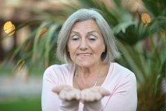 Older woman showing your product Stock Photos