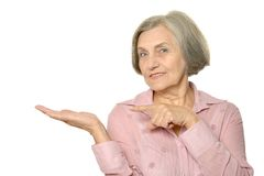 Older woman showing. Your product on a white background Stock Photo