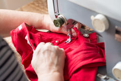 Older woman si fixing red jeans on a sewing machine. Royalty Free Stock Photography