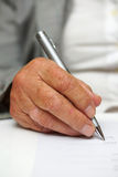 Older woman signing the document Stock Photography