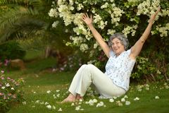 Older woman sitting with flowers Stock Image