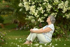 Older woman sitting with flowers Stock Photos