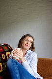 Older woman sitting at home enjoying cup of tea Royalty Free Stock Photos