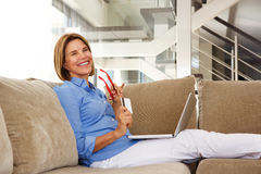 Older woman sitting at home with laptop and credit card Stock Photos