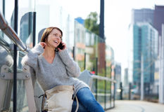 Older woman sitting outside in the city talking on mobile phone Royalty Free Stock Images