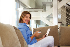 Older woman sitting on sofa with bowl of breakfast and tablet Royalty Free Stock Image
