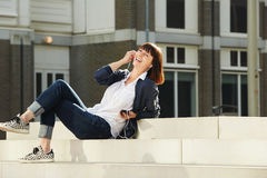 Older woman sitting on steps listening to music Stock Photography
