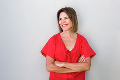 Older woman smiling against gray wall with arms crossed Stock Images