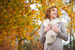 Older Woman Smiling in Autumn. Older woman smiling with yellow leaf background Stock Photos