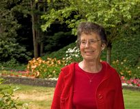 Older Woman Smiling In Garden Setting Royalty Free Stock Photography