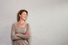 Older woman standing with arms crossed looking away smiling Royalty Free Stock Photography