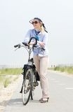 Older woman standing with bicycle on path on summer day Royalty Free Stock Photos