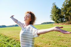 Older woman standing outside with arms raised smiling royalty free stock image