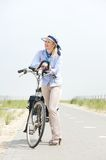 Older woman standing relaxing with bicycle on path Stock Images