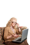 Older woman studying finances. On a laptop computer Royalty Free Stock Photo