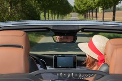 Older woman with sun hat and her partner in a convertible car. Older women with sun hat and her partner in a convertible car on a sunny day stock photo