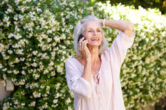 Older woman talking on phone with hand to head outside Royalty Free Stock Photography