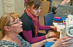 Older Woman Teaching Younger Woman to Sew stock photo