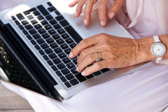 Older woman typing on laptop computer Stock Photos