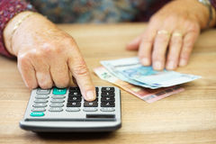 Older woman is using calculator to calculate all expenses royalty free stock photography