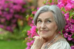 Older woman on walk with pink flowers Royalty Free Stock Image