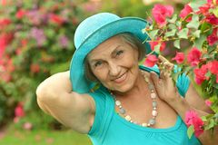 Older woman on walk with red flowers Stock Image