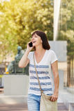Older woman walking outside talking on mobile phone in city Stock Photos