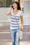 Older woman walking outside talking on phone in city Stock Image