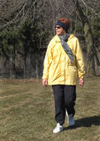 Older woman walking in winter. Older woman with red hair – wearing a yellow coat, scarf, and headband-  walking on a cold sunny winter day, looking to her Stock Photos