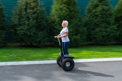 Woman with white hair riding personal transporter stock image