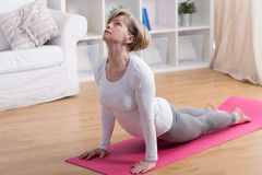 Older woman and yoga. Older active woman exercising yoga in the morning Stock Image