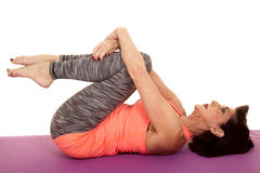 Older woman yoga on back curl knees. An older woman stretching out her back by doing yoga Royalty Free Stock Images