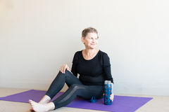 Older woman after yoga. Older woman in black yoga clothing smiling and relaxing on purple mat with blue glass water bottle after yoga Royalty Free Stock Photo