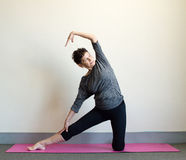 Older woman in yoga side stretch Stock Photography
