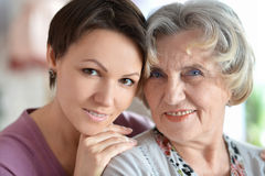Older woman and a young woman. Close-up portrait of a happy older women and a young woman royalty free stock photos