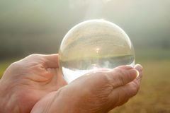 Older womans hand holding a shiny glass sphere Royalty Free Stock Photo