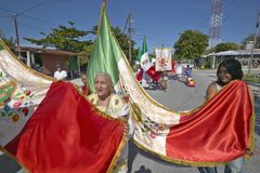Older women and children marching through streets of Puerto Morelos carrying Mexican flag and Catholic statues, Yucatan Peninsula, Stock Images