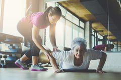 Older women doing push ups. Looking at camera. Stock Image