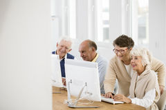 Woman standing next to friend. Older women with glasses standing next to her friend in computer classroom Stock Photography