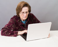 Older Women Using the Computer. An older woman trying to figure out how to surf the Internet Royalty Free Stock Photos