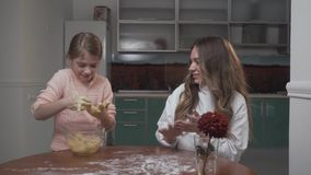Older and younger girls kneading dough on a table in the kitchen.. Two sisters prepare vegetable salad while sitting at stock video footage